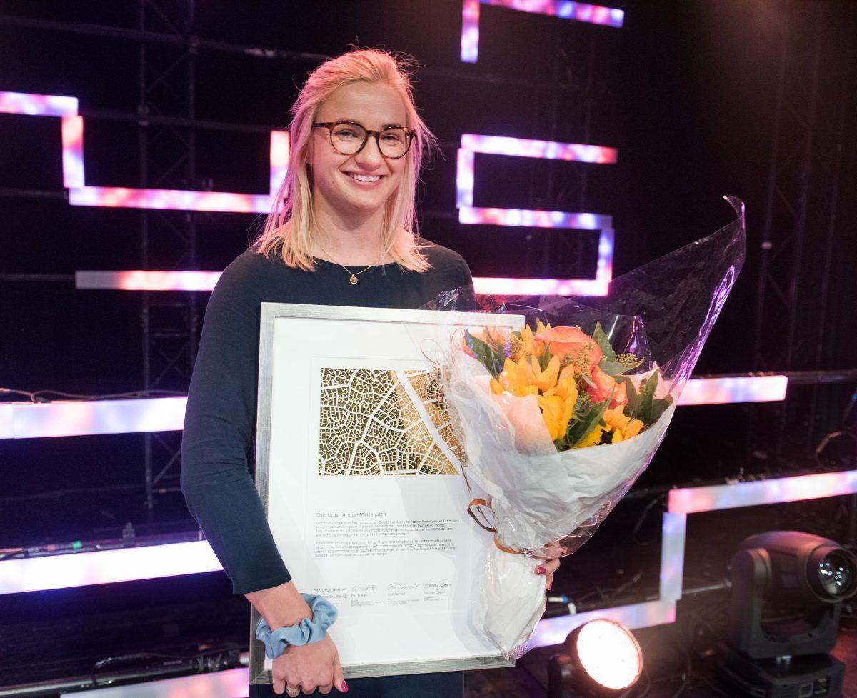 Emily Coch Fjeldstad med diplom og blomster. Hun er vinner av Aspelin Ramm-prisen 2019